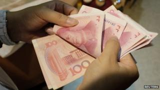 File photo: A woman counts Chinese yuan notes at a market in Beijing, 1 July 2013