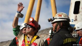Chilean miner Alex Vega (left), the 10th of 33 miners to leave the mine, waves upon surfacing from the San Jose mine, near Copiapo, on 13 October, 2010