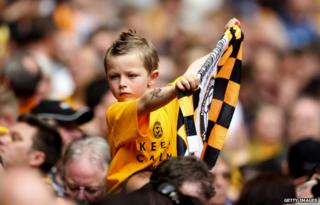 Young Newport fan holds up a flag during match between Wrexham and Newport County A.F.C at Wembley Stadium on 5 May 2013