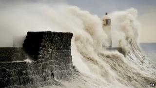 Huge waves crash against the harbour wall and engulf the lighthouse at Porthcawl