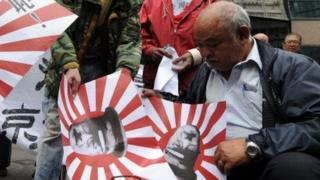 """Chinese Protesters burn Japanese """"rising sun"""" naval flags outside the Japanese Embassy in Hong Kong on December 13, 2013."""