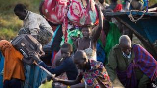 Displaced people disembark from the river barges that brought them from Bor to Awerial in South Sudan on 2 January 2014