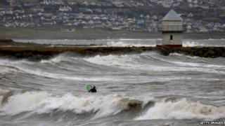 A surfer in rough waves at Porthcawl on Sunday