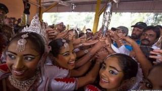 Dawnswyr traddodiadol yn Sri Lanka yn dathlu gyda'r baton.