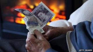 An elderly man holding cash in front of a gas fire