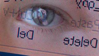 Child's eye reflected in computer screen