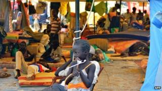 A South Sudanese child stands next to a tent within the United Nations Mission in Juba on 4 January 2014