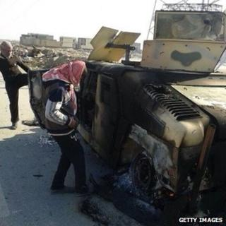 Iraqis inspect the burnt out remains of an Iraqi army APC on the highway leading to Ramadi