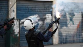 Bahraini police officers fire tear gas during a protest in Sanabis (3 December 2013)