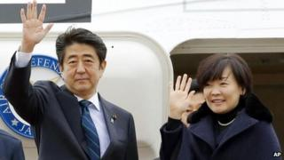 Japanese Prime Minister Shinzo Abe, center, and his wife Akie wave as they depart for Africa, at Haneda Airport in Tokyo Thursday, Jan. 9, 2014.