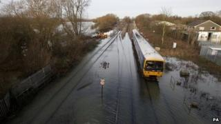 Train travels over flooded tracks in Oxford on Wednesday