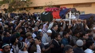 Pakistani government officials and comrades carry the coffin of police officer Chaudhry Aslam during his funeral in Karachi on January 10, 2014.