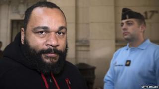 Dieudonne M'bala M'bala (L) arrives for his trial at the Paris courthouse on December 13