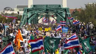 Anti-government protesters make their way across Buddhayodfah bridge during a warm-up rally to paralyse the capital in Bangkok, Thailand (9 Jan 2014)