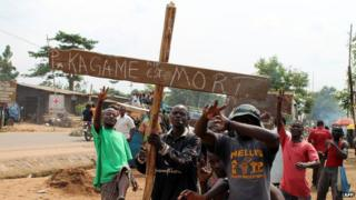 "Residents in Goma hold a cross saying ""Kagame is dead"" on hearing false rumours that the Rwandan president had died"