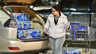 Charleston resident Niru Parikshak loads up the back of her car with bottled water 9 January 2014