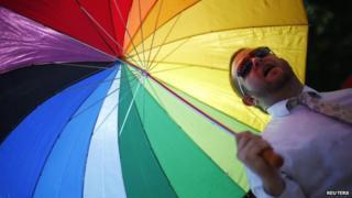 A man under a multi-coloured umbrella