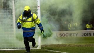A steward removes a flare at Fir Park