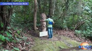A visitor touches the cardboard statue