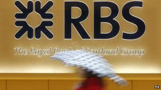 A person walks past an RBS sign carrying a brolly