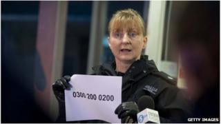 Supt Liz McAinsh holds up the Child Rescue Alert system telephone number