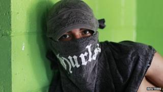 A member of the Barrio 18 gang poses for a photograph at a bakery in a neighbourhood in Ilopango, El Salvador
