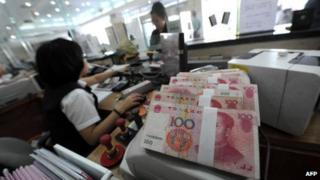 A worker counting yuan notes in a bank in China