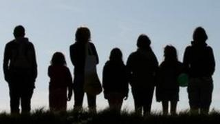 Silhouettes of a group of people in a line