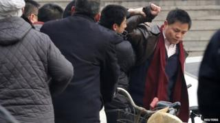 Zhang Xuezhong (right), a lawyer for Zhao Changqing, argues with plain-clothed policemen as he refuses to show them his identification card when he was stopped and questioned by them on his way to court to attend Mr Zhao's trial in Beijing, 23 January 2014