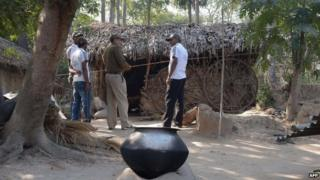 Police officials stand near the alleged crime scene following a gang-rape in Subalpur village in Birbhum district, on January 24, 2014.