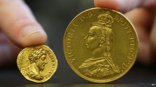 A coin from the reign of Emperor Marcus Aurelius and a £5 Victoria coin