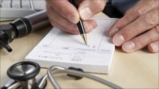 A GP writing a prescription