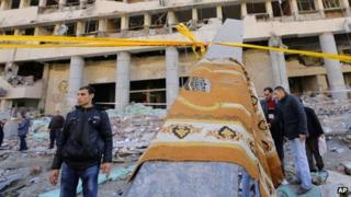 A prayer carpet hangs on a piece of rubble at the site of a blast at the Egyptian police headquarters in downtown Cairo, Egypt, Friday, Jan. 24, 2014.