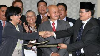 Miriam Coronel Ferrer (L), chairperson of the government negotiating panel, exchanges documents with MILF Chief Negotiator Monagher Iqbal (R) during a press conference at a hotel in Kuala Lumpur on January 25, 2014.