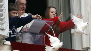 Pope Francis watches as two children release the doves during the Angelus prayer in Saint Peter's Square at the Vatican