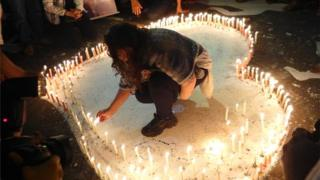The heart formed by 242 candles in front of the Kiss nightclub during the overnight vigil