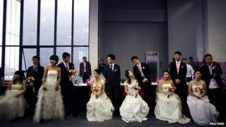 Couples wait to participate in a staged mass wedding, organised as part of a matchmaking event to inspire singles to get married, at a suburban area of Shanghai, 18 May 2013