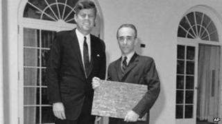 President John F Kennedy poses with artist Jasper Johns at the White House in Washington as Johns holds a bronze sculpture of his iconic 1960 Flag painting