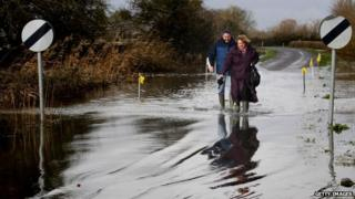 A couple approach flood water on the road at Burrow Bridge, Somerset