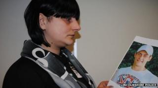 Oksana Zdanovica-Rjabisenkova with a picture of her brother Ivans Zdanovics
