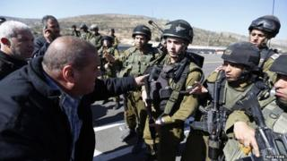 A Palestinian man confronts Israeli soldiers next to the Palestinian village of Ein Sariya after the shooting of Mohammed Mubarak (29 January 2014)