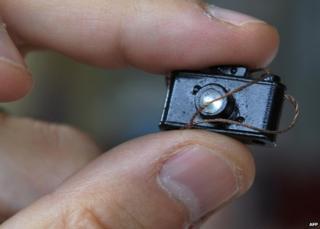 Man holds tiny model camera