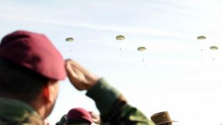 A member of the Parachute Regiment salutes a parachute drop by 3 Para, at Pegasus Memorial, in Ranville, Normandy, to mark the 65th anniversary of the D-Day landings.