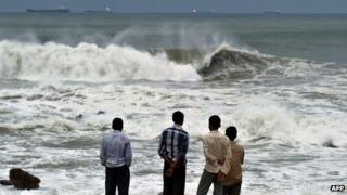 Men watch waves crash on beach in India
