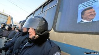 Ukrainian police stand next to a bus with an opposition poster stuck to the window