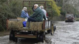 A tractor carries residents along a flooded road from the village of Thorney on the Somerset Levels
