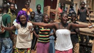 The wife and sister of a Christian man killed by anti-Balaka combatants after he was mistaken for a Muslim react as his body (not pictured) is transported on a cart in Bangui on 29 January 2014