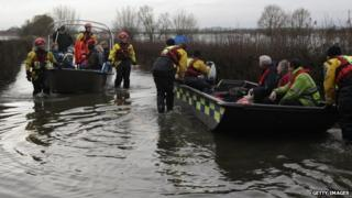 People in a boat on a flooded field