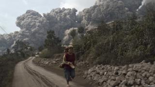 A villager run as Mount Sinabung erupt at Sigarang-Garang village in Karo district, Indonesia's North Sumatra province, February 1