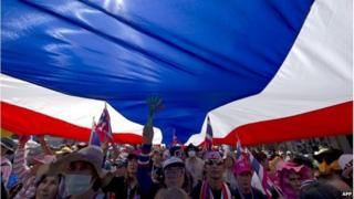 Thai anti-government protesters carry a large national flag as they parade during a rally in Bangkok on January 25